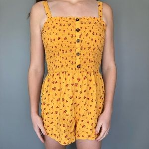 yellow button down romper with rose flower design